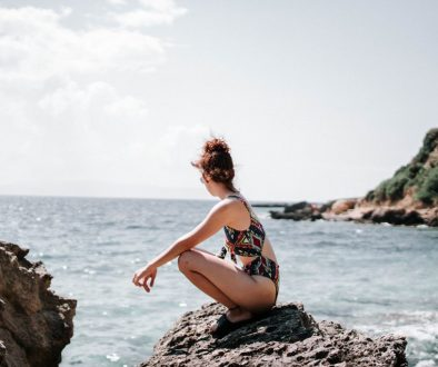 Canva - Woman in Swim Suit Sitting on a Rock