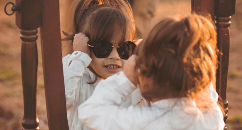 Canva - Girl in White Long-sleeved Shirt Wearing Sunglasses Facing Mirror