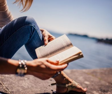 Canva - Woman Wearing Blue Denim Jeans Holding Book Sitting on Gray Concrete at Daytime